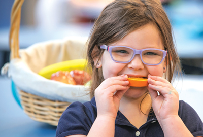Jillian Fortney, a kindergarten student at St. Agnes School in Charleston, W.Va., eats an orange slice during lunch