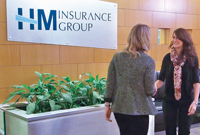 Two women greeting each other in the lobby of HM Insurance Group