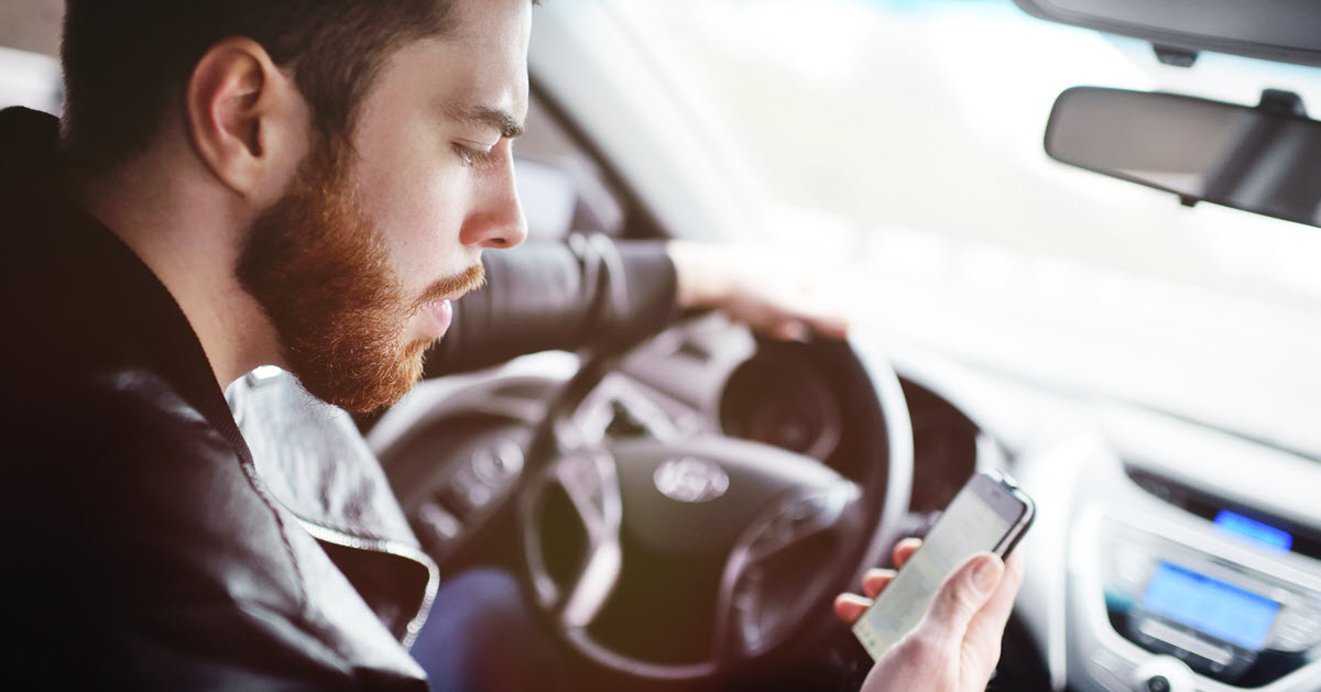 A man looking at his mobile phone while driving