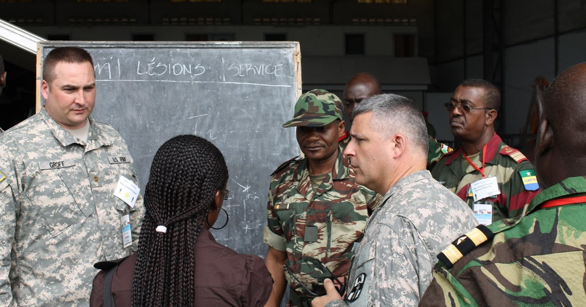 Tony and a group of people in Cameroon, Africa having a discussion in front of a blackboard